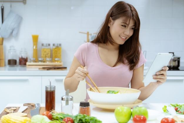 Jovem mulher asiática ler informações do estudo tablet para cuidar de sua saúde, comendo salada e frutas em vez de comer gordura e calorias