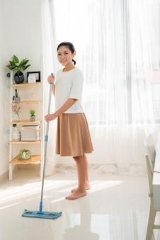 Jovem mulher asiática limpando o chão em casa fazendo tarefas com um sorriso atraente no rosto.