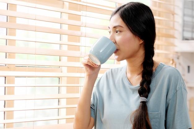 Jovem mulher asiática linda tomando café em pé pela janela na cozinha