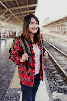 Jovem mulher asiática mochileira caminhando sozinha na plataforma da estação de trem com a mochila