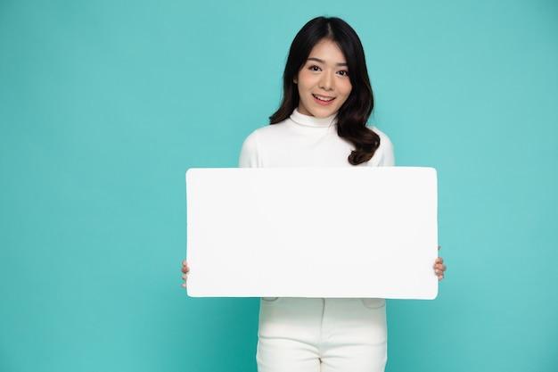 Jovem mulher asiática mostrando e segurando um quadro branco em branco isolado na parede verde