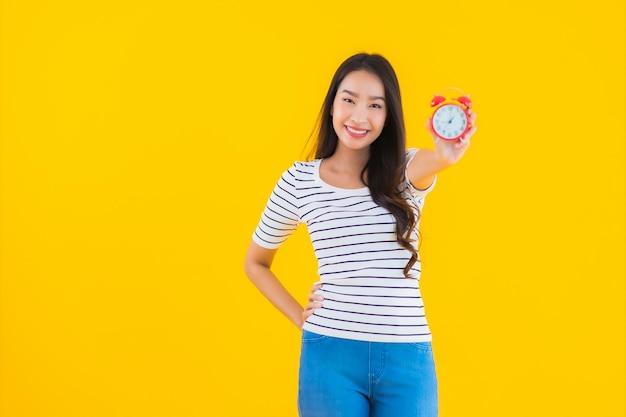Jovem mulher asiática mostrar relógio ou alarme