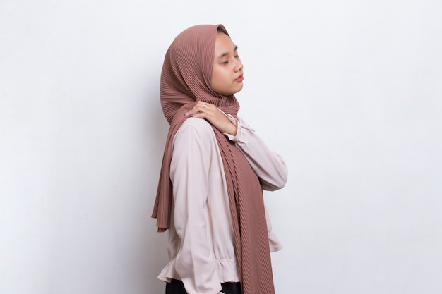 Jovem mulher asiática muçulmana com conceito médico de lesão e dor no pescoço e ombro