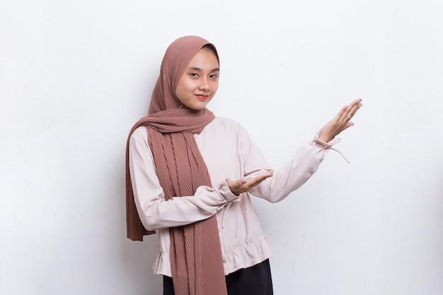 Jovem mulher asiática muçulmana feliz apontando com os dedos para diferentes direções no fundo branco