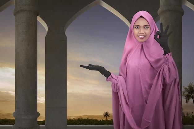 Jovem mulher asiática muçulmana mostrando a área vazia para copyspace