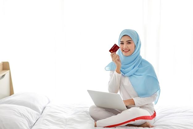 Jovem mulher asiática muçulmana sentada na cama e segurando o cartão de crédito com o computador no quarto.