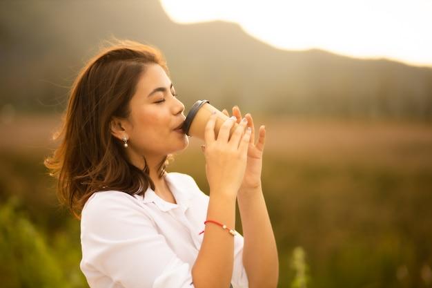 Jovem mulher asiática na camisa branca, bebendo café ao ar livre no horário de verão do nascer do sol