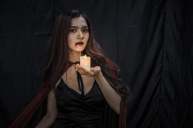 Jovem mulher asiática na fantasia de bruxa e segurar a vela no fundo de pano preto do conceito de halloween. retrato de mulher adolescente vestida de bruxa para celebrar o festival de halloween.