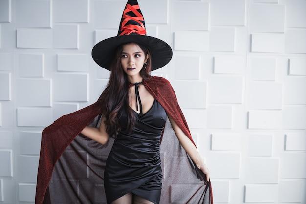 Jovem mulher asiática na fantasia de bruxa na parede branca do conceito de halloween. retrato de mulher adolescente vestida de bruxa para celebrar o festival de halloween.