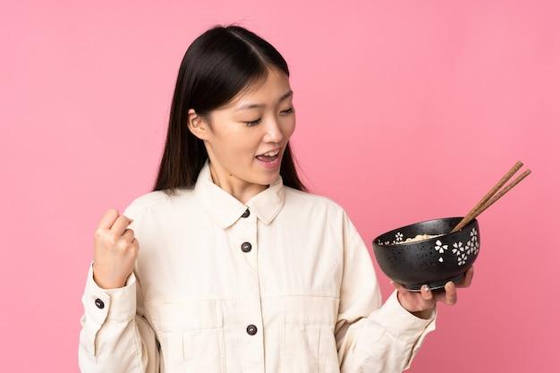 Jovem mulher asiática na parede rosa, comemorando uma vitória, mantendo uma tigela de macarrão com pauzinhos