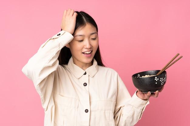 Jovem mulher asiática na parede rosa percebeu algo e pretendendo a solução enquanto segura uma tigela de macarrão com pauzinhos