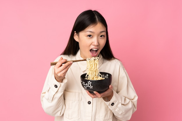 Jovem mulher asiática na parede rosa, segurando uma tigela de macarrão com pauzinhos e comê-lo