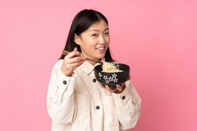 Jovem mulher asiática na parede rosa, segurando uma tigela de macarrão com pauzinhos