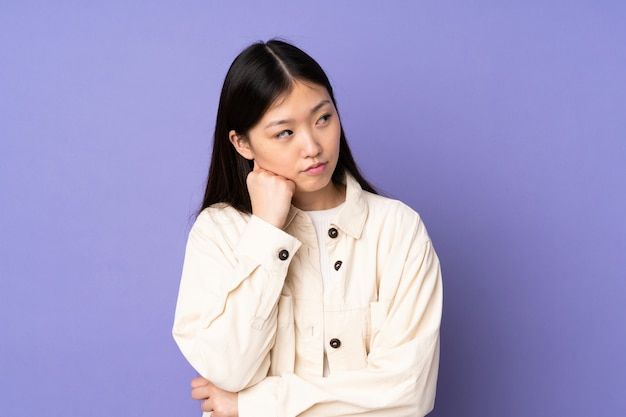 Jovem mulher asiática na parede roxa com expressão cansada e entediada