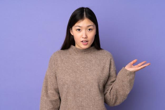 Jovem mulher asiática na parede roxa, fazendo o gesto de dúvidas