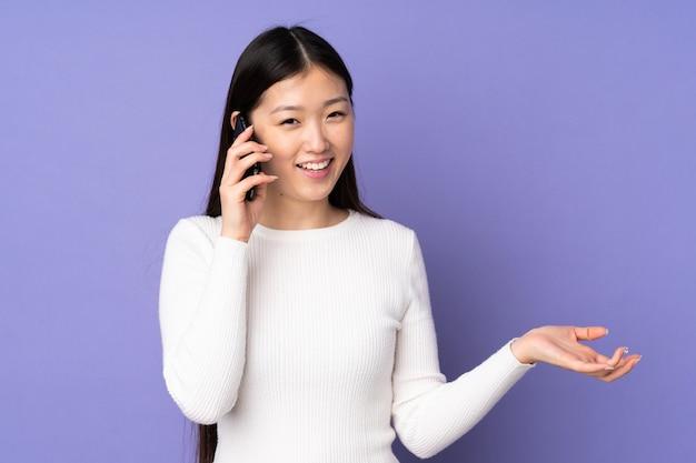Jovem mulher asiática na parede roxa, mantendo uma conversa com o telefone móvel com alguém
