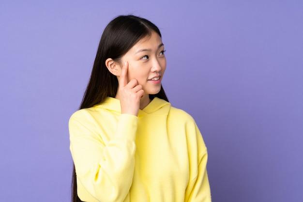 Jovem mulher asiática na parede roxa, pensando uma idéia enquanto olha para cima