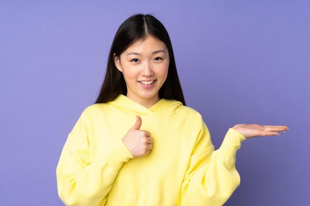Jovem mulher asiática na parede roxa segurando espaço em branco