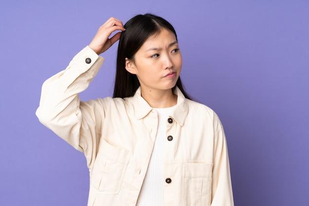 Jovem mulher asiática na parede roxa, tendo dúvidas ao coçar a cabeça