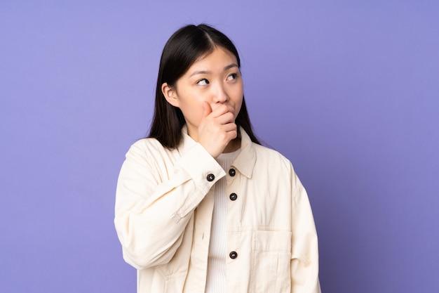 Jovem mulher asiática na parede roxa, tendo dúvidas e com a expressão do rosto confuso