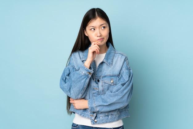 Jovem mulher asiática na parede, tendo dúvidas e pensando
