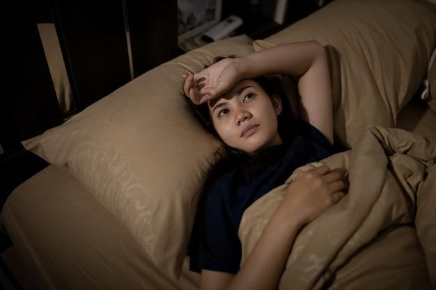 Jovem mulher asiática não consegue dormir a insônia tarde da noite. não consigo dormir. apnéia do sono ou estresse. conceito de distúrbio do sono.