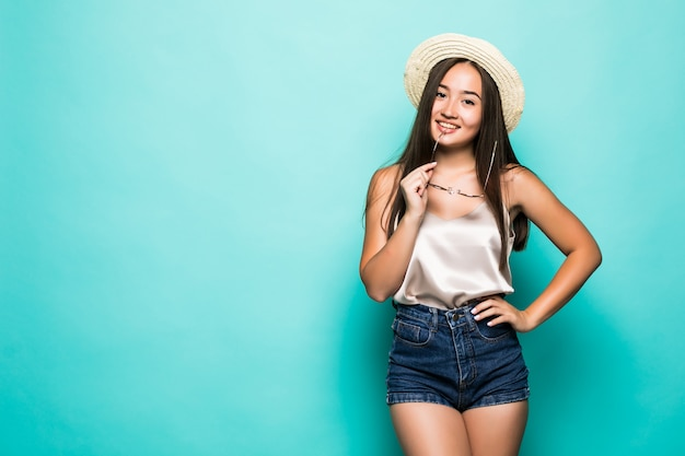 Jovem mulher asiática no chapéu e óculos de sol sorrindo fundo turquesa