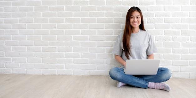 Jovem mulher asiática no estilo casual usando o computador portátil