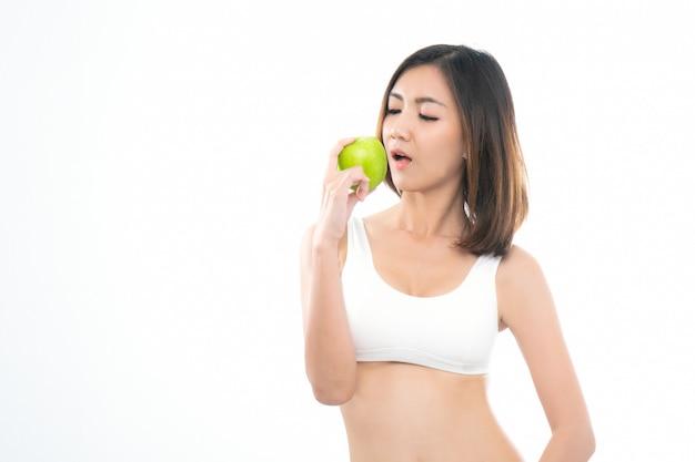 Jovem mulher asiática no sutiã branco do esporte que come a maçã verde.