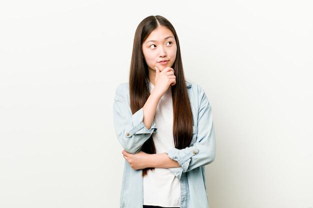Jovem mulher asiática olhando de soslaio com expressão duvidosa e cética.