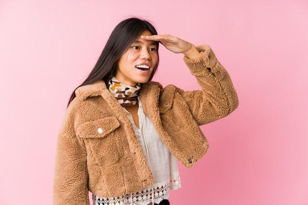 Jovem mulher asiática olhando longe mantendo a mão na testa