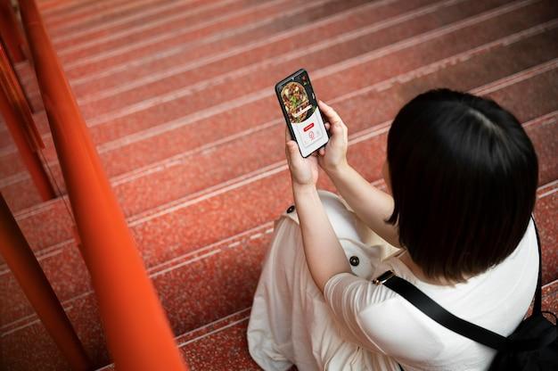 Jovem mulher asiática olhando para um aplicativo em seu telefone