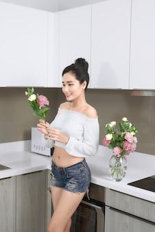 Jovem mulher asiática organizando flores na cozinha.