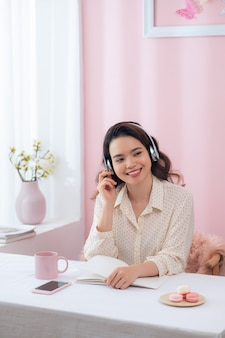 Jovem mulher asiática ouvindo música e escrevendo em seu escritório.
