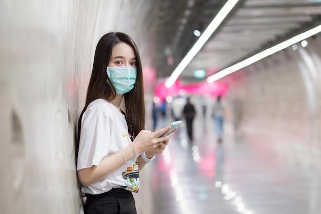 Jovem mulher asiática parada no túnel do metrô e usa máscara facial como uma nova normal e de saúde