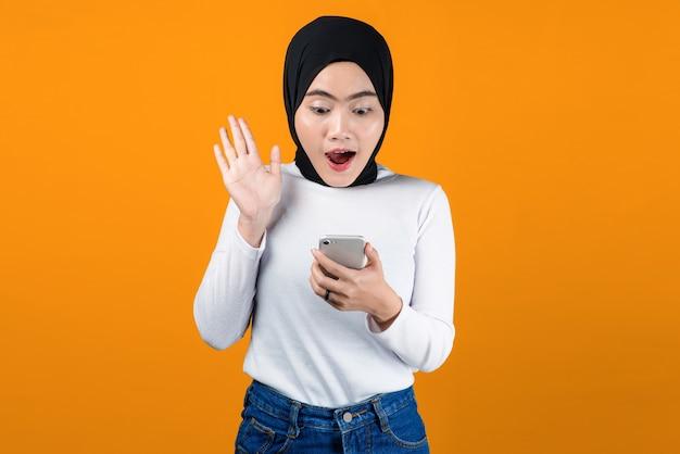 Jovem mulher asiática parece chocada ao usar o celular