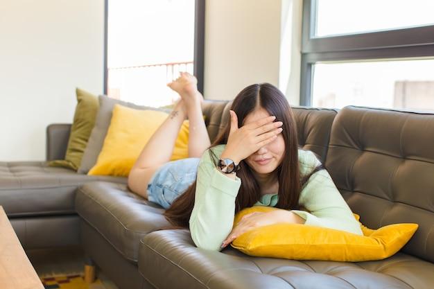 Jovem mulher asiática parecendo estressada, envergonhada ou chateada, com dor de cabeça, cobrindo o rosto com a mão