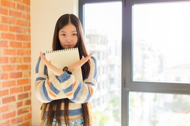 Jovem mulher asiática parecendo irritada e cansada de sua atitude, dizendo o suficiente! mãos cruzadas na frente, dizendo para você parar