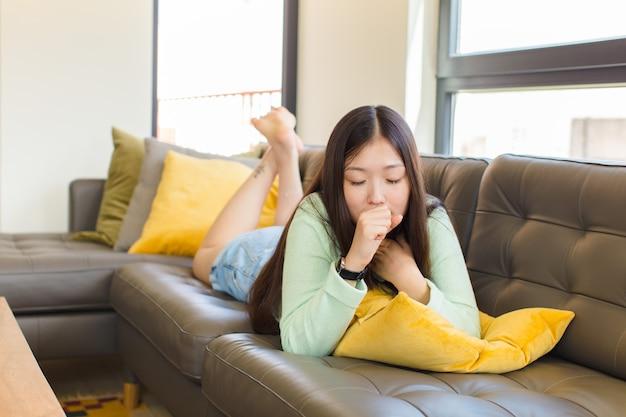 Jovem mulher asiática passando mal, com dor de garganta e sintomas de gripe, tosse com a boca coberta