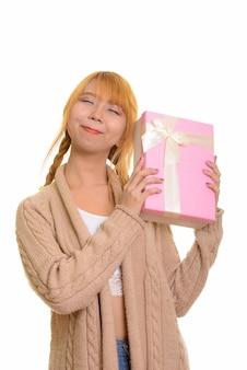 Jovem mulher asiática pensativa adivinhando uma caixa de presente