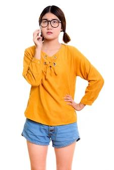 Jovem mulher asiática pensativa em pé enquanto fala no celular