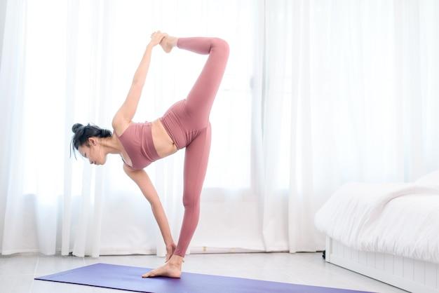 Jovem mulher asiática pratica ioga para reduzir o esforço, trabalhando em casa em um quarto.