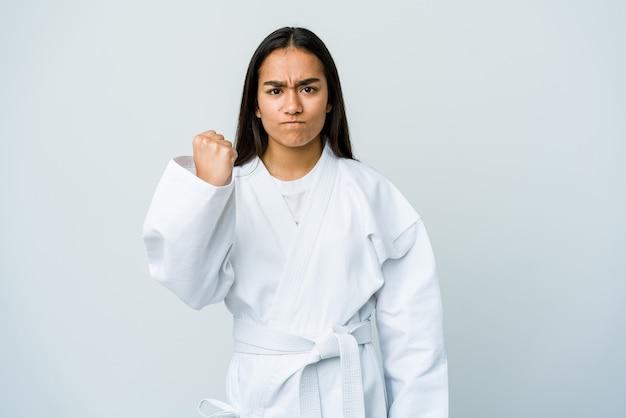 Jovem mulher asiática praticando caratê, isolada na parede branca, mostrando o punho para a frente, expressão facial agressiva
