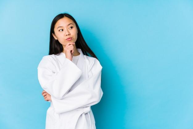 Jovem mulher asiática praticando karatê, olhando de soslaio com expressão duvidosa e cética