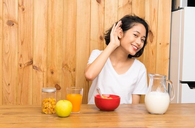 Jovem mulher asiática que come o leite do café da manhã que escuta algo