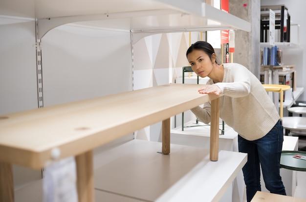 Jovem mulher asiática que escolhe a mobília em uma loja moderna das mobílias para a casa