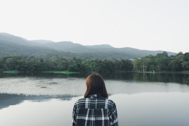 Jovem mulher asiática que está de cara o mar. sentindo-se realmente solitário, de coração partido