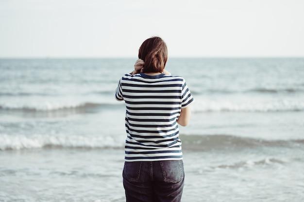 Jovem mulher asiática que está de cara o mar. sentindo-se realmente solitário