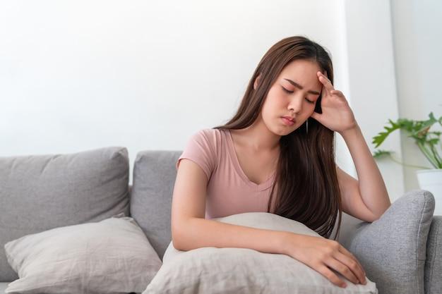 Jovem mulher asiática que guarda sua cabeça, ela tem uma dor de cabeça que senta-se no sofá do sofá na sala de visitas em casa.