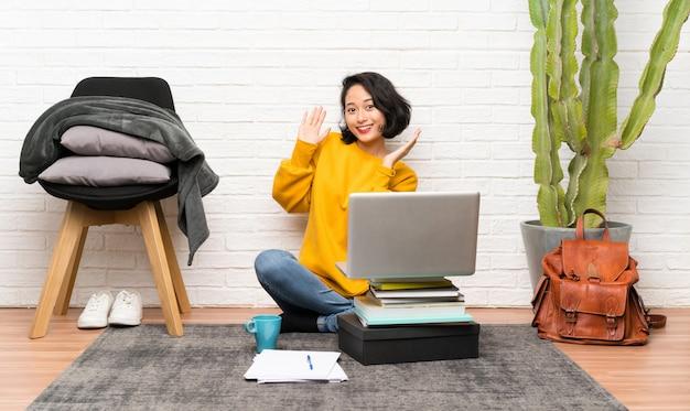 Jovem mulher asiática que senta-se no assoalho com expressão facial da surpresa